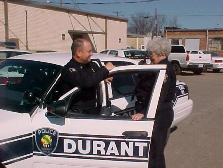 Police Officer Speaking with Chaplain in front of Durant Police Car